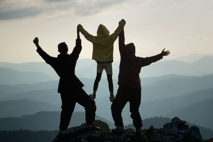 triumphant family on top of a mountain