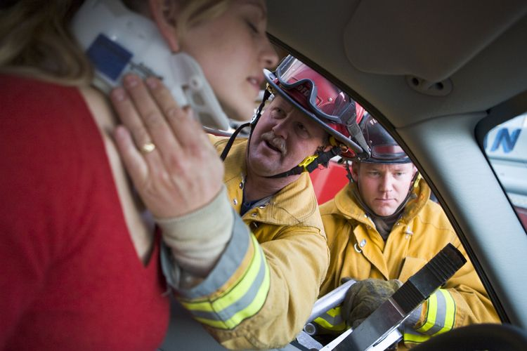 fire fighter assists car accident victim