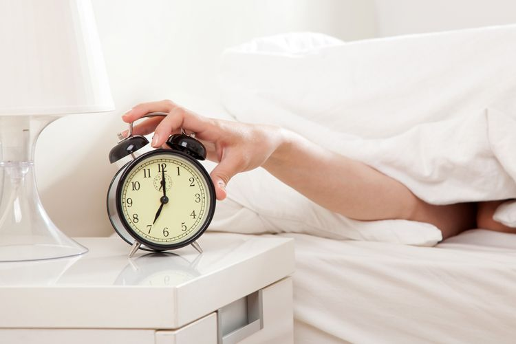 hand reaching for alarm clock