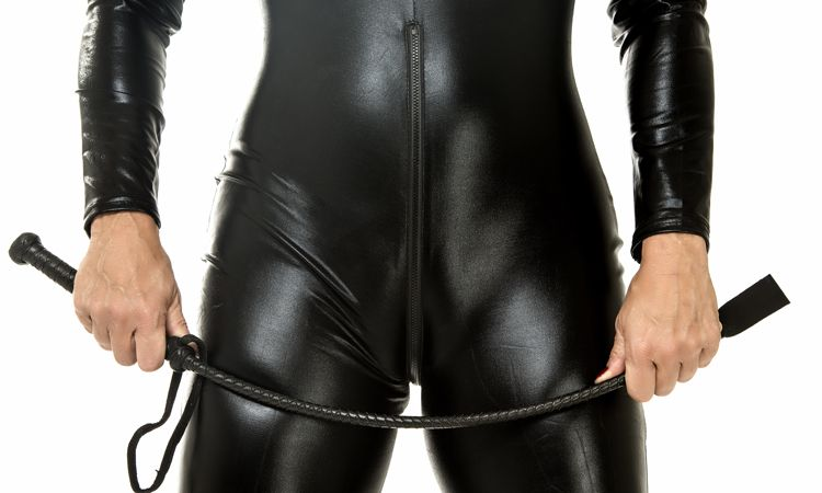 woman in catsuit bending whip