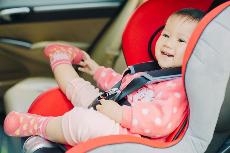 smiling baby in a car seat