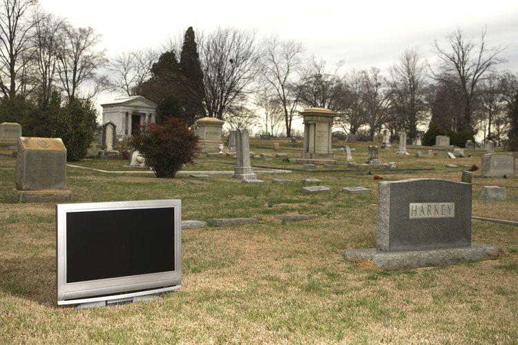 flatscreen next to a headstone in a cemetery