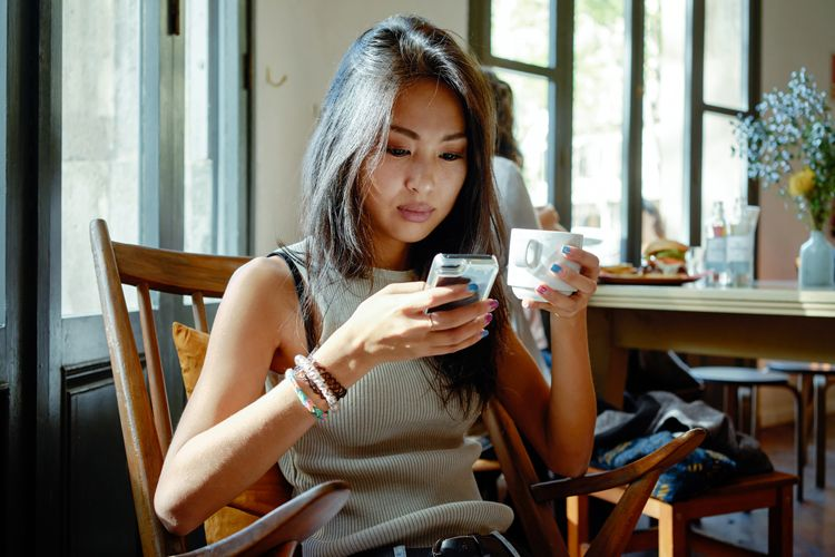 young woman checking her phone in a cafe